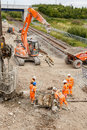 Construction workers moving helical pile drill screws ilkeston england august on site next to a section of railway track in Stock Photography