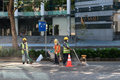 Construction workers repair pavement on a downtown street.