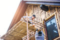 Construction workers thermally insulating house facade with glass wool standing on scaffold Stock Photography