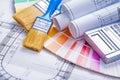 Consturction paint concept close up view on paintbrushes rolled blueprints calculator color palette Stock Image
