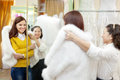 Consultant helps bride chooses fur cape at shop Stock Photo