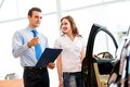 Consultant in the showroom and the buyer car salesman declares a young girl advantages of new car Royalty Free Stock Images