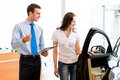 Consultant in the showroom and the buyer car salesman declares a young girl advantages of new car Royalty Free Stock Photo
