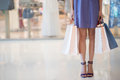 Consumerism concept legs of female shopaholic holding many paper bags Royalty Free Stock Photos