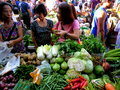 Consumers buy from a vegetable vendor in a market in cainta rizal philippines asia december photo of Stock Photos