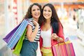 Consumers in the mall gorgeous girlfriends with paperbags looking at camera trade center Royalty Free Stock Photo