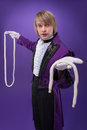 Consummate mastery of magician half length portrait fair haired concentrated juggler wearing splendid violet jacket and white Royalty Free Stock Photo