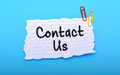 Contact us hand written on paper with blue background Royalty Free Stock Photo