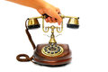 Contact us now picking up the brass receiver of a vintage antique wooden phone to Stock Images