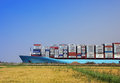 Container ship huge passing suez canal in egypt beside land Stock Photos
