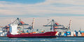 Container ship passing cranes in Rotterdam harbor Royalty Free Stock Photo