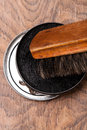 Container of shoe polish and brush on wooden Royalty Free Stock Photography