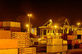Containers at night with cranes loading a ship in the background Stock Photography