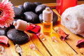 Containers and oil balls for body care brown gradient background essences with black stones towel sheets on wooden base Stock Photos
