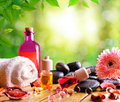 Containers and oil balls and essences for body care with black stones towel sheets on wooden base green leaves bokeh Stock Images