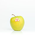 Contaminated apple yellow ripe savory labeled as bio hazardous against a white background Stock Photo