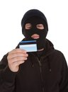 Contemplating burglar holding credit card wearing mask over white background Stock Photo