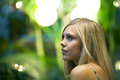 Contemplative blonde woman young under warm tungsten lighting shallow depth of field Royalty Free Stock Photo