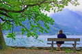 Contemplative woman alone on bench admiring the landscape Stock Photos