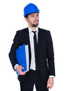 Contemplative young architect or engineer structural standing holding a large binder in a suit and hardhat as he thinks about the Stock Images