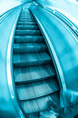 Contemporary escalator stairs with commuters stepping on fisheye view blue toned Royalty Free Stock Image