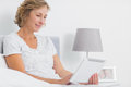 Content blonde woman sitting in bed using tablet pc at home bedroom Royalty Free Stock Image