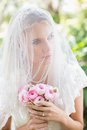 Content bride wearing veil over face holding rose bouquet in the countryside Royalty Free Stock Images