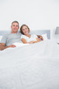 Content couple cuddling in bed looking at camera home bedroom Stock Images