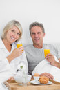 Content couple having orange juice at breakfast in bed looking camera Stock Image