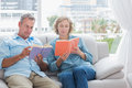 Content couple reading books on the couch at home in living room Stock Images
