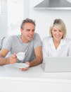 Content couple using laptop in the morning sitting at kitchen counter Royalty Free Stock Photo