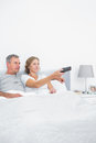 Content couple watching tv in bed at home bedroom Royalty Free Stock Photos