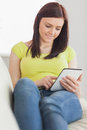 Content girl sitting on a sofa using a tablet pc brunette looking and Stock Photography