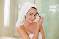 Content natural brown haired woman brushing her eyebrows in a bright bathroom Stock Image