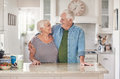 Content seniors standing in each other`s arms together at home