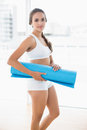 Content sporty brunette holding an exercise mat in bright room Royalty Free Stock Image