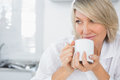 Content woman having coffee in the morning sitting kitchen at home Stock Images