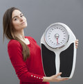 Content young woman holding scales health and fitness chic s girl standing next to her weighting scale for kilos or pounds control Stock Photo