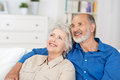 Contented elderly couple sitting reminiscing in a close embrace in their living room and recalling happy nostalgic memories Royalty Free Stock Image