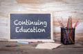 Continuing Education text on a blackboard. Old wooden table with texture Royalty Free Stock Photo