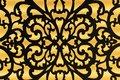The contour of a metal lattice with an ornament on a yellow background