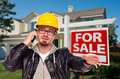 Contractor in Hard Hat in Front of House and Sign Stock Image