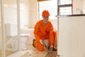 Contractor removing floor tiles handsome young old in bathroom Stock Photos
