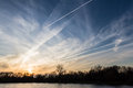 Contrail or chemtrail beautiful sunset over the lake with what looks like manufactured cloud formations from airplanes all over Royalty Free Stock Images