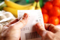 Control of till receipt closeup view a person s hands looking and checking her Stock Photography