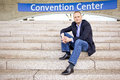 Convention attendee smart casually dressed sitting on the steps of a center Royalty Free Stock Images