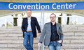 Convention attendees two smart casual dressed colleagues posing on the steps in front of a center Stock Images