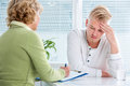Conversation with a therapist doctor talking to her male patient at office Stock Photos