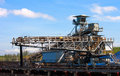 Conveyor belt carrying coal and emptying onto a huge pile large Royalty Free Stock Photography