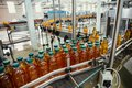 Conveyor line with plastic bottles of juice at modern factory equipment. Beverage manufacturing plant interior inside Royalty Free Stock Photo